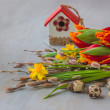 Stock Photo: Easter eggs with birdhouse and spring flowers