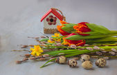 Easter eggs with birdhouse and spring flowers — Stock Photo