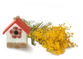 Decorative birdhouse and mimosa — Stock Photo