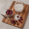 Harvest raspberries and sugar on a cutting board — Stock Photo #44674329