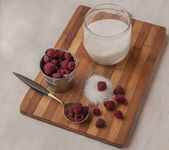 Harvest raspberries and sugar on a cutting board — Stock Photo