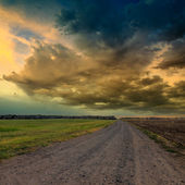 Road in meadows and and dramatic sky — Stock Photo