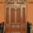 Beautiful carved wooden mahogany door in a brick wall — Stock Photo #42389727