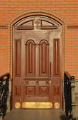 Beautiful carved wooden mahogany door in a brick wall — Stock Photo