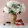 Ripe cherries and strawberries with bouquet of peonies — Stock Photo #47191429