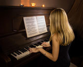 Girl playing the piano by candlelight — Stock Photo