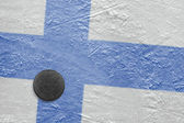 Finnish flag and the puck on the ice — Stock Photo