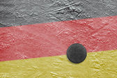 Germany flag and puck on ice — Stok fotoğraf