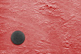Hockey puck on ice red  — Stock Photo