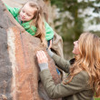 Mom helping her little daughter to climb a rock — Stock Photo