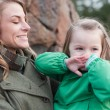 Happy little girl covering mouth with hands held by her mother — Stockfoto