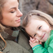 Happy girl resting on mom's shoulder — Stock Photo