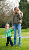 Young mother and toddler daughter at the park — Stock Photo