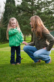 Smiling girl holding mother's hand at the park — Stock Photo