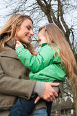Smiling mother and daughter at the park — Stock Photo