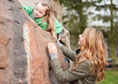 Mom helping her little daughter to climb a rock — Foto Stock