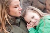Garota feliz, descansando no ombro da mãe — Fotografia Stock