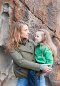 Toddler girl sitting on mother's hip against rock wall — Stock Photo