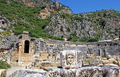 Mask, rock tombs and ancient theater in Myra, Turkey — Stock Photo