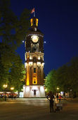 Old fire tower with clock at night — Stok fotoğraf