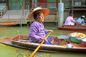 Unidentified woman is sails in the floating market along raft houses at the river Kwai in Kanchanaburi, Thailand. — Stock Photo