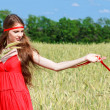 Girl in the wheat field with red tape — Stock Photo