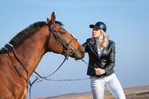 Woman fondles horse — Stock Photo