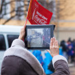 Stock Photo: January 11, 2014, Saratov, Russia. Olympic Torch Relay Sochi 2014. Womshoots video with tablet