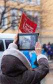 January 11, 2014, Saratov, Russia. Olympic Torch Relay Sochi 2014. Woman shoots video with a tablet — Stock Photo