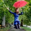 Young woman jump with red umbrella — Stock Photo