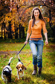 A beautiful woman and his dogs posing outside — Stock Photo
