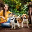 A beautiful young woman and his dogs posing outside — Stock Photo