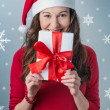 Stock Photo: Christmas woman holding gifts wearing Santa hat