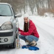 Woman applying Snow Chains — Stok fotoğraf