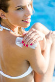 Woman applying lotion — Stock Photo