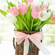 Pink and white tulips in a wicker basket — Stock Photo