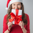 Christmas woman holding gifts wearing Santa hat — Stockfoto