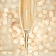 Glass of champagne against golden background — Stock Photo #28762667