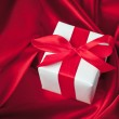Valentines gift box tied with a red satin ribbon bow on red satin background — Stock Photo #28765137