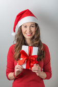 Christmas woman holding gifts wearing Santa hat — Stock Photo