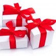 White gift boxes with red ribbon isolated on white — Stock Photo
