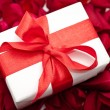 Gift box over red colorful rose petals — Stock Photo