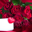 A bunch of roses with a blank card for congratulations. — Stock Photo #28779751