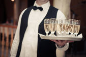 Professional waiter in uniform is serving champagne — Stockfoto