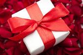 Scatola regalo sopra petali di rosa colorati rossi — Foto Stock