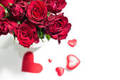 Red roses in vase and chocolate candies for Valentine's Day — Stock Photo