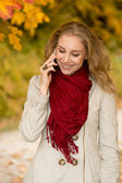 Happy young woman on cell phone in autumn park — Stock Photo