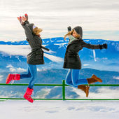 Happy girls jumping over snow background — Stockfoto