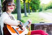 Jonge vrouw zittend op een veld en het spelen van gitaar — Stockfoto