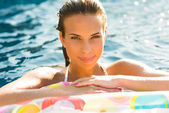 Menina de beleza relaxante na piscina usando o colchão — Fotografia Stock
